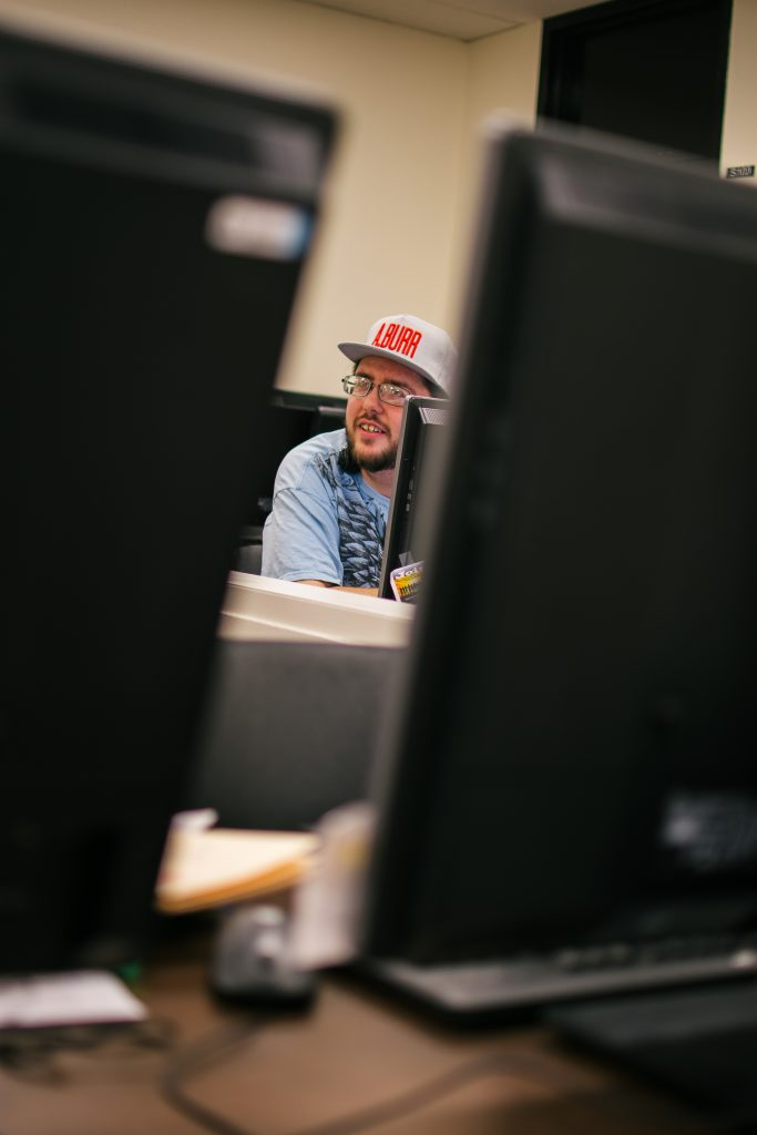 Between two computers, a student is featured in discussion