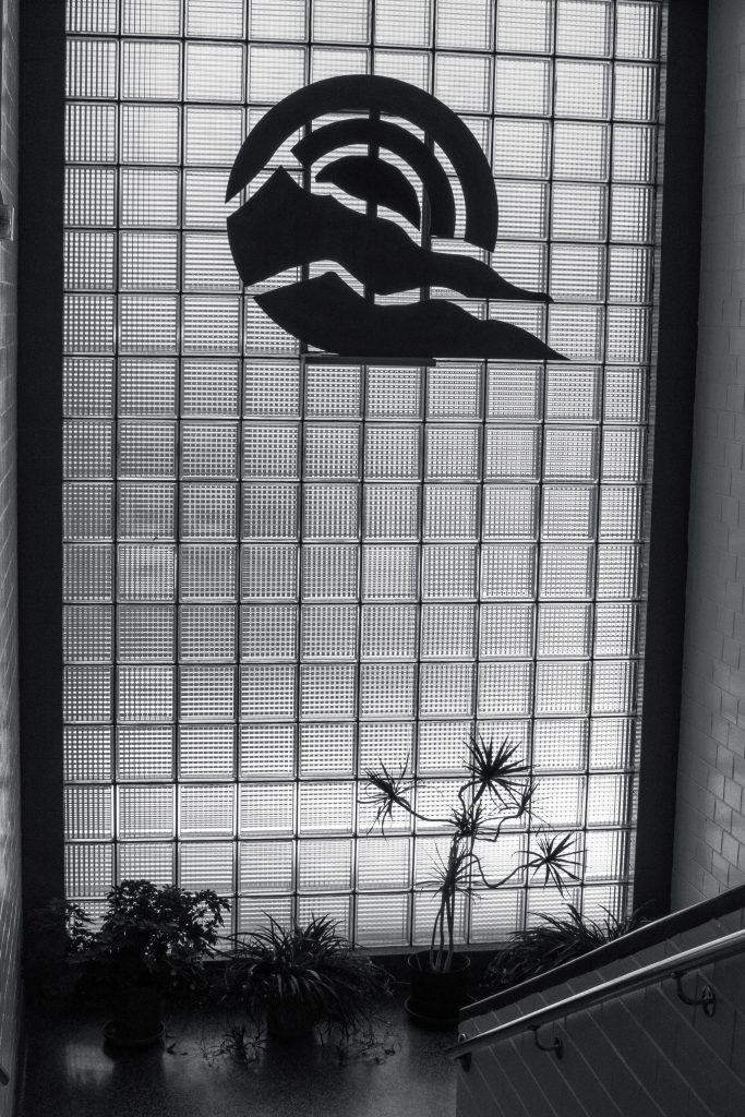 A glass wall in which PPCC's emblem shines through. Black and white photo.