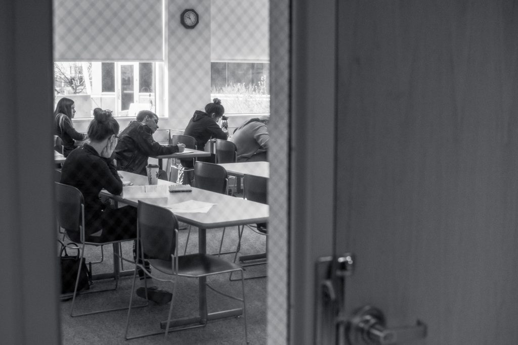 The photo shows students in a classroom hard at work. Black and white.
