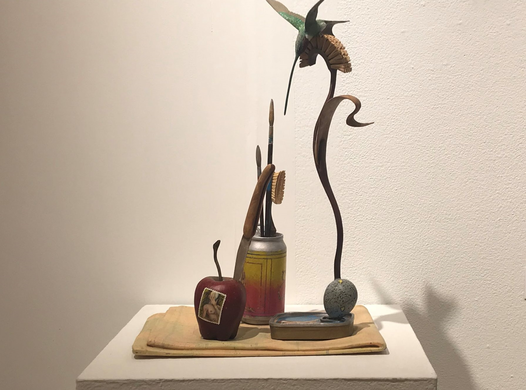 A sculpture with an apple, bird, and leaf