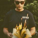 This is an image of a man standing with a burning book.