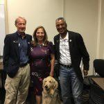 Local politicians Tony Exum, Yolanda Avila, and Senator Pete Lee stand with a golden retriever