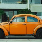 This is an image of an old orange Volkswagen Beetle.